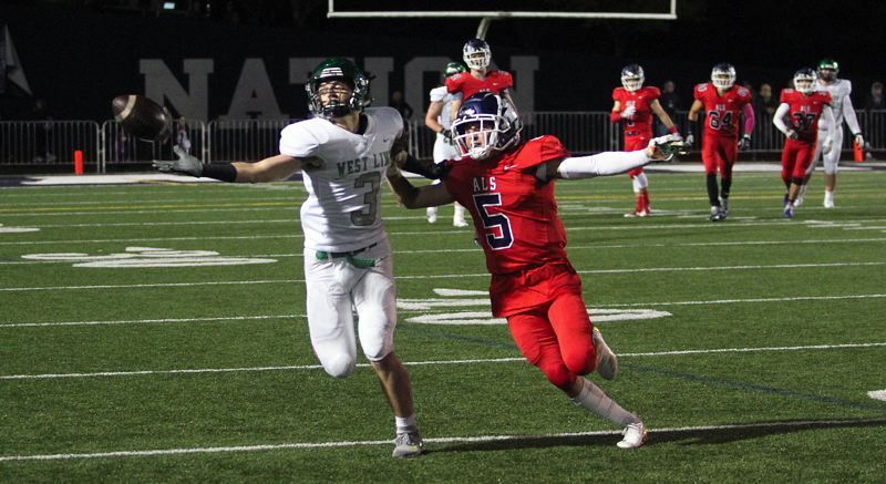 PAMPLIN MEDIA GROUP PHOTO: MILES VANCE - West Linn's Casey Tawa (left) tries to make a catch while defended by Lake Oswego's Matt Sebolsky during the Lakers' 41-28 win at Lake Oswego High School on Friday.