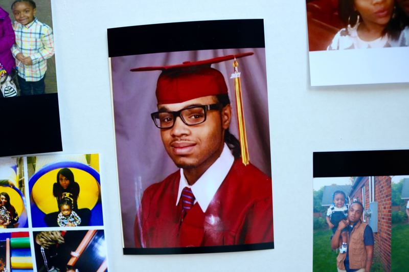 TRIBUNE PHOTO: ZANE SPARLING - Photos of Patrick Kimmons, including one from his high school graduation, are displayed at a memorial at the corner of the Southwest Third Avenue and Harvey Milk Street in downtown Portland.