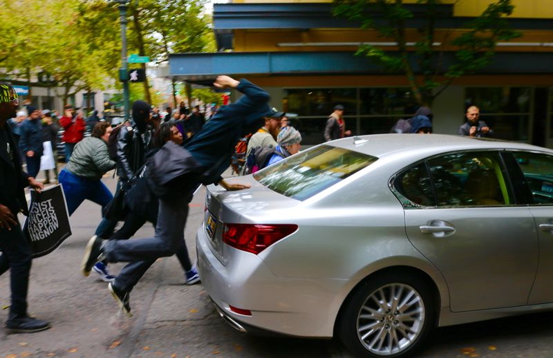 TRIBUNE PHOTO: ZANE SPARLING - A protester slams the trunk of a silver sedan that had rammed into several protesters blocking traffic on Southwest Third Avenue on Saturday, Oct. 6 in Portland.