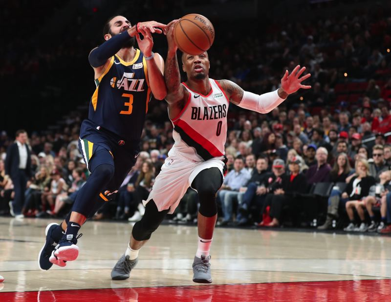 TRIBUNE PHOTO: JAIME VALDEZ - Trail Blazers guard Damian Lillard (right) strips the ball from Utah Jazz guard Ricky Rubio in the first half Sunday night at Moda Center.