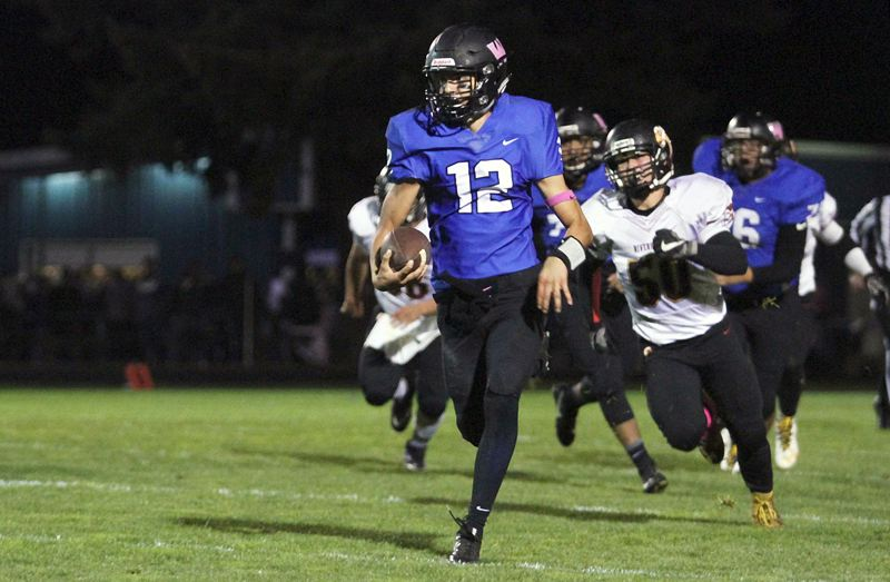 INDEPENDENT PHOTO: PHIL HAWKINS - Woodburn senior quarterback R.J. Veliz takes the ball 12 yards up the middle of the field for a touchdown duing his team's 14-13 loss to The Dalles on Friday.