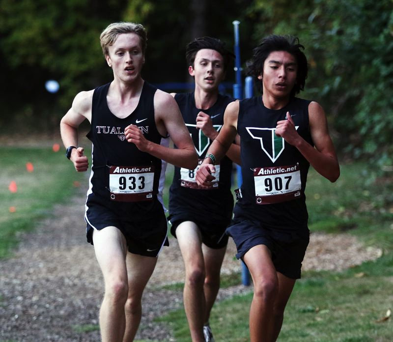 TIMES PHOTO: DAN BROOD - From left, Tualatin's Graehm Alberty, Tigard's Cole Grieb and Tigard's Oscar Nieves Lira race for the lead at last week's Three Rivers League cross country meet.