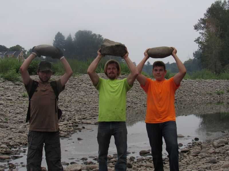 SUBMITTED PHOTO - Justin Jorgensen, Joshua Beckham and Aiden NcNiece hoisted rocks over their heads when they participated in a previous clean-out of the channel leading to Clackamette Cove.