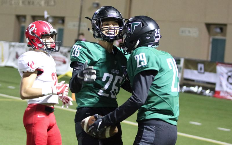 PMG PHOTO: JIM BESEDA - Tigard's Jazz Ross (26) celebrates with Luke Ness after Ness caught a 36-yard touchdown pass from Drew Carter to give the Tigers a 62-20 lead with 3:13 remaining the third quarter of Friday's game.