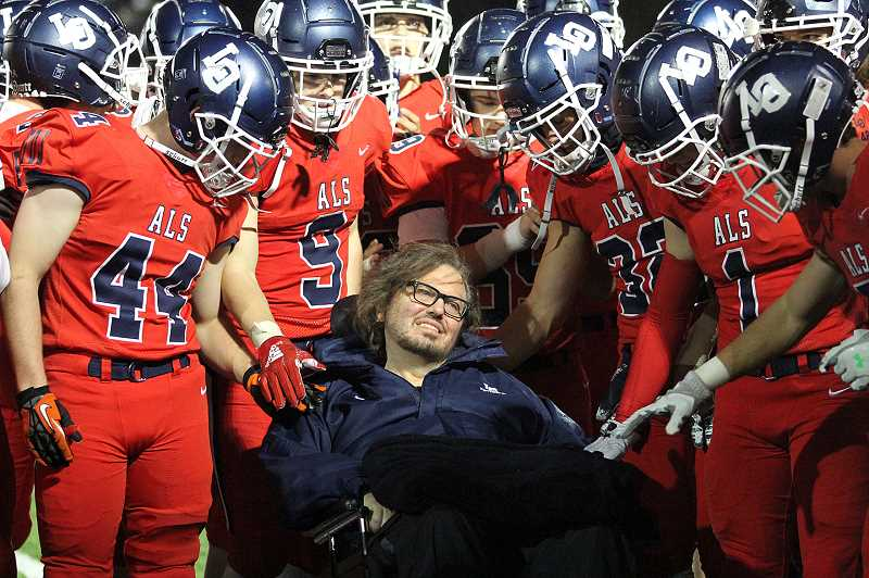 REVIEW PHOTO: MILES VANCE - Lake Oswego High football players wore red uniforms Friday night to honor assistant coach Jeff Young, who has battled Amyotrophic Lateral Sclerosis (ALS) for more than three decades.