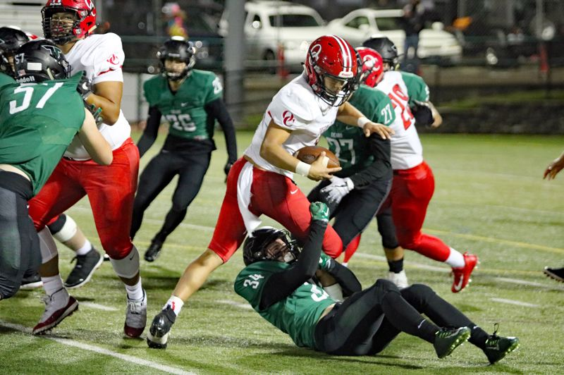 PMG PHOTO: JIM BESEDA - Tigard linebacker Cole Scott (34) drops Oregon City quarterback Colby Iverson for a 1-yard loss during the Tigers' 62-27 win on Friday.