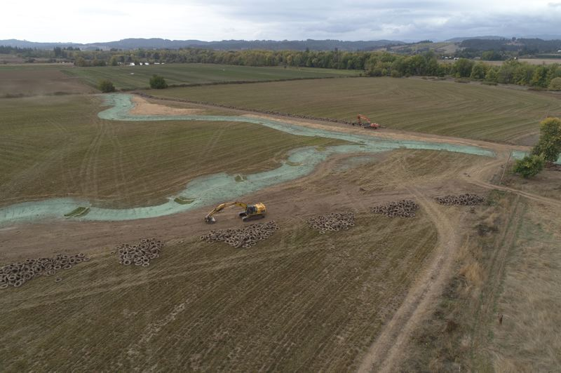 COURTESY PHOTO: CLEAN WATER SERVICES - An aerial shot of the Spring Hill Natural Area shows a construction vehicle, stacks of tires and a blue-green material called hydroseed, a mixture of native plant seeds, mulch and soil binding agents.