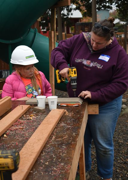 OUTLOOK  PHOTO: MATT DEBOW  - Tiffany Kallgren shows her 6-year-old daughter Victoria how to use a drill during a volunteer day at Imagination Station on Sunday, Oct. 7.