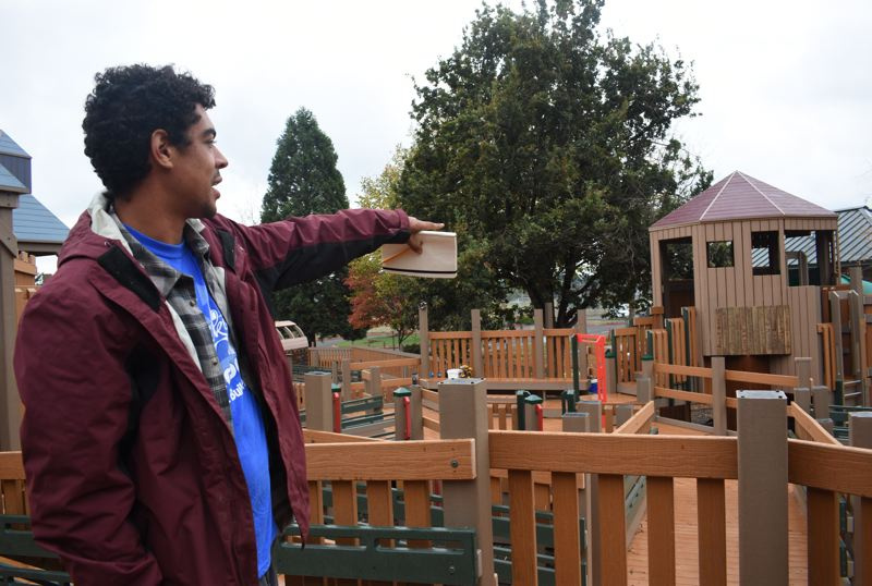 OUTLOOK PHOTO: MATT DEBOW - Taj Leathers points to the main play area of Imagination Station, 1900 S.W. Cherry Park Road on Sunday, Oct. 7. Leathers estimates the park is about 70 percent complete, and crews will finish the project in approximately a week if it stays dry outside.