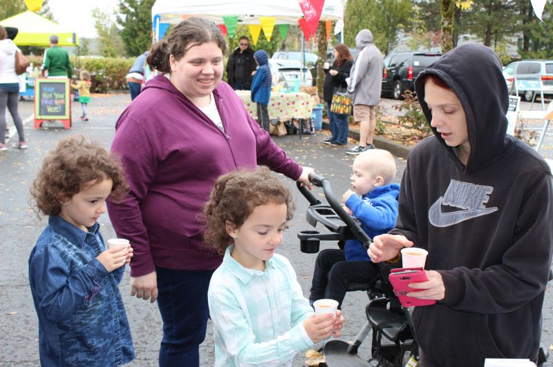 PHOTO BY KIMBERLY JACOBSEN NELSON - Families enjoyed sampling over 800 cups of juice they helped make by pressing the apples donated by local vendors.