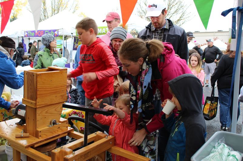 PHOTO BY KIMBERLY JACOBSEN NELSON - Hundreds of families lined up for their turn on the old-fashioned apple press during the eighth-annual cider event at the Oregon City Farmers Market.