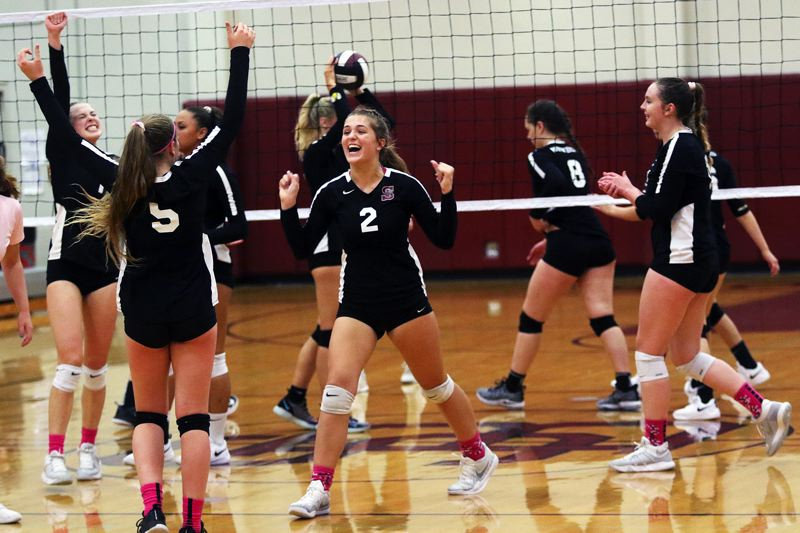 TIMES PHOTO: DAN BROOD - Members of the Sherwood volleyball team, including junior Piper Harrop (5) and junoir Allison Fiarito (2) celebrate during the squad's second-set comeback against Newberg.