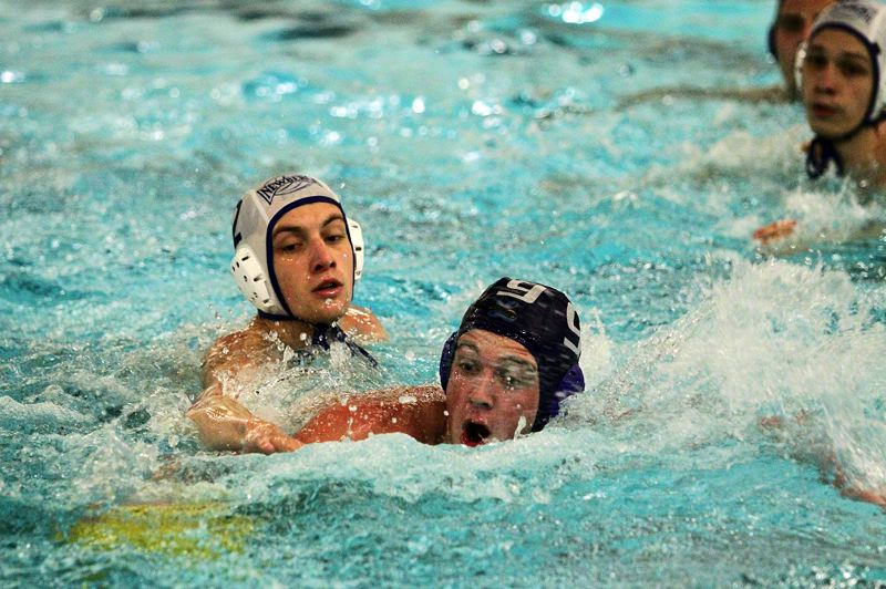 REVIEW PHOTO: MILES VANCE - Lakeridge's Thomas Gooding races past Newberg's Raleigh Day to get the ball during his team's 8-7 overtime loss at Lake Oswego School District Pool on Monday.