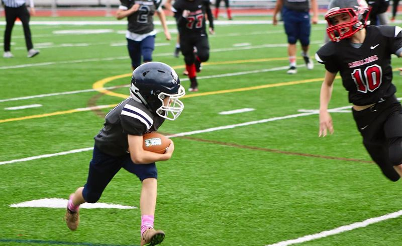 SUBMITTED PHOTO - Lake Oswego 5/6 running back Sawyer Best prepares to make a Clackamas defender miss on his way to the end zone for a touchdown on Saturday.