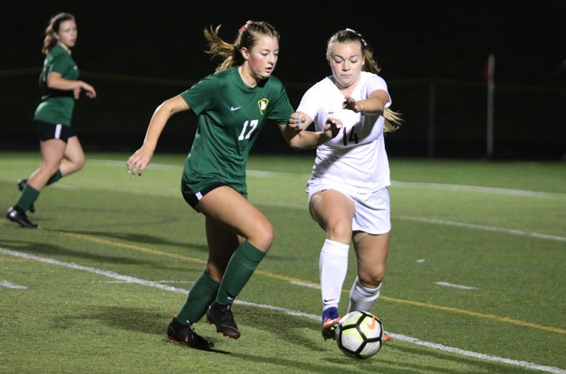 PAMPLIN MEDIA: JIM BESEDA - Putnam's Kyla Miller (17) and Milwaukie's Mackenzie Ware (14) battle for a loose ball during the second half of Tuesday's Northwest Oregon Conference girls' soccer match at Putnam High School.