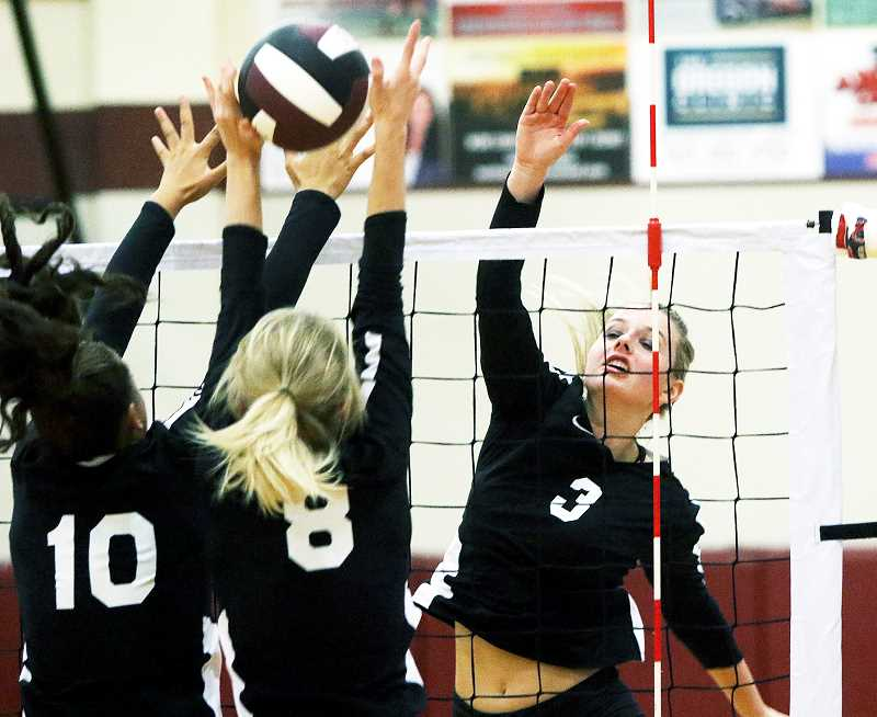 DAN BROOD - TIGARD/TUALATIN TIMES - Senior Giselle Benetti slams a kill through the Sherwood block during Newberg's 3-2 road win Monday night, which put the Tigers just a half game behind the Bowmen and Liberty for second place in the Pacific Conference.