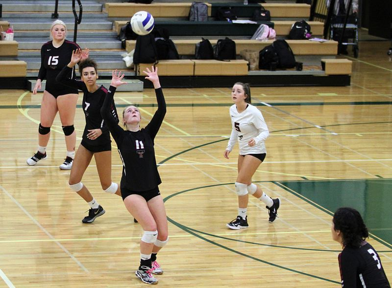 PMG PHOTO: MILES VANCE - Tualatin High School junior Jackie Phillips (11) sets the ball during the Wolves' Three Rivers League match at West Linn on Tuesday.
