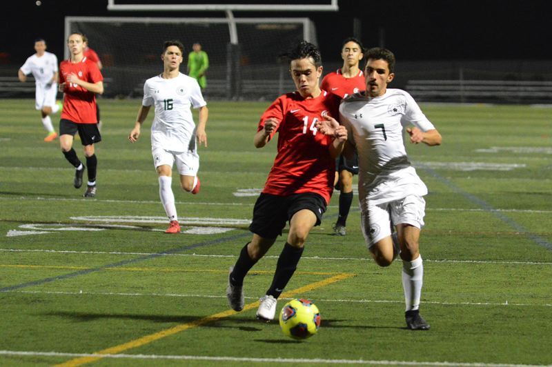 OUTLOOK PHOTO: DAVID BALL - Reynolds Harith Al Obaide chases alongside Clackamas defender Maxwell van der Bosch for a ball played into the Raiders attacking zone in the first half of Mondays 3-3 draw.