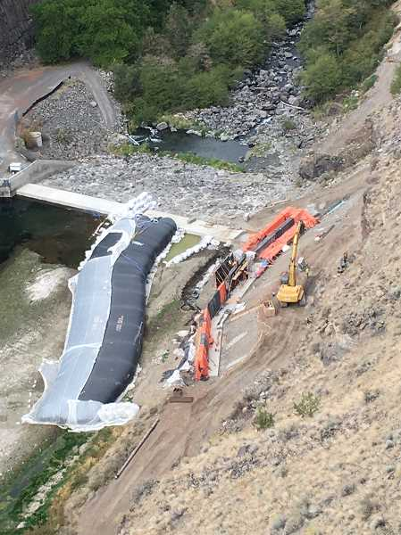 SUBMITTED PHOTO - On Friday, crews work to raise the height of the Opal Springs Dam by three feet in order to install a fish ladder which will enable fish to travel up the Crooked River for the first time since the 1960s.