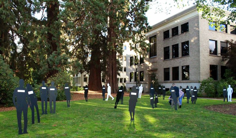 STAFF PHOTO: OLIVIA SINGER - Silhouettes spread across the courthouse lawn represented people in Oregon who have lost their lives to domestic violence in the past year and a half.