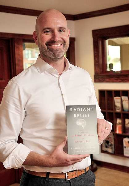 REVIEW PHOTO: VERN UYETAKE  - P. Brendon Lundberg poses with his book 'Radiant Relief: A Case for A Better Solution to Chronic Pain,' which explains the treatments he offers through his Radiant Pain clinics.