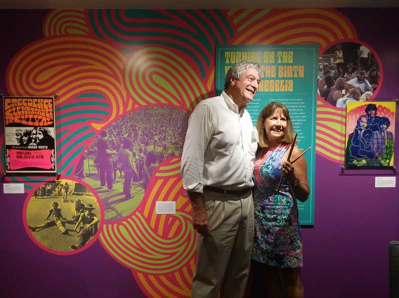 SUBMITTED PHOTO: SCOTT GLAZER - Peter and Cyndie Glazer attend the opening of 'Portland Psychedelic,' an exhibit at the Oregon Historical Society that features memorabilia donated by the Glazers. Cyndie Glazer is holding drumsticks that Peter was given on July 26, 1967, by Doors drummer John Densmore when Glazer was on stage talking with Jim Morrison and the rest of the band  after a concert.