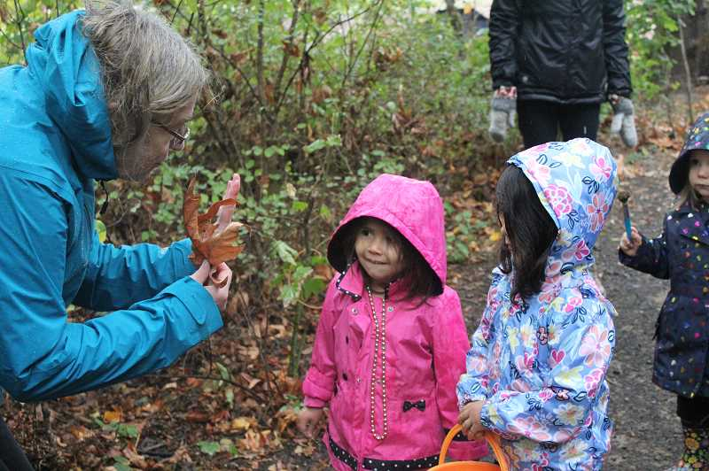 REVIEW PHOTO: COREY BUCHANAN - Guide Sue Thomas teaches Lucy Cervantes (left), Penny Cervantes (middle) and Reina Santiago about leaves during a Preschool Nature Walk through Springbrook Park last week.