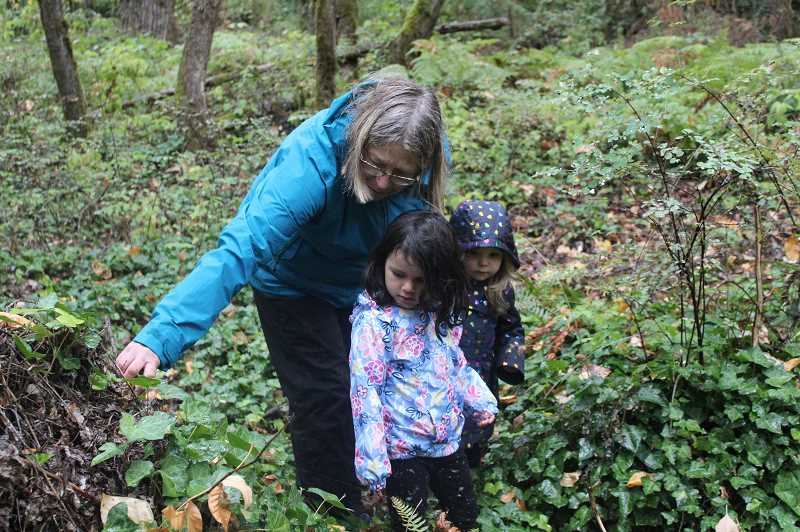 REVIEW PHOTO: COREY BUCHANAN - Sue Thomas (left) shows a 'cave' to Penny Cervantes (middle) and Reina Santiago during their Preschool Nature Walk last week.