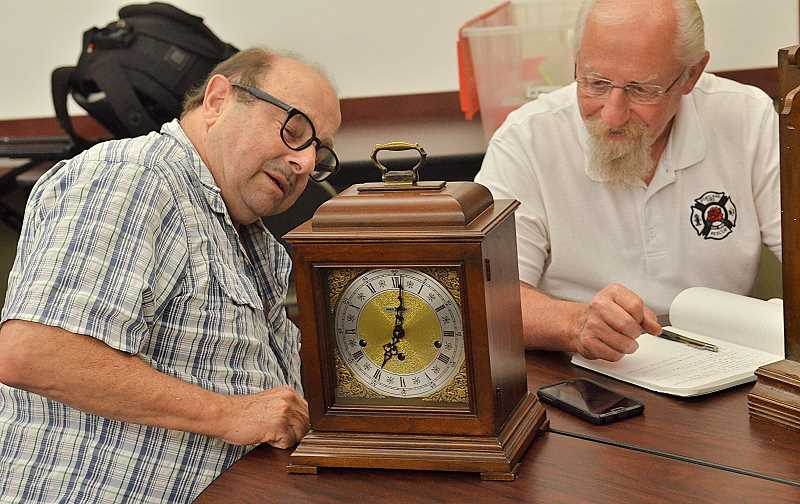TIDINGS PHOTO: VERN UYETAKE - Chris Hartman, left, checks to see how his 30-year-old clock is running while chatting with Chuck Harrison.