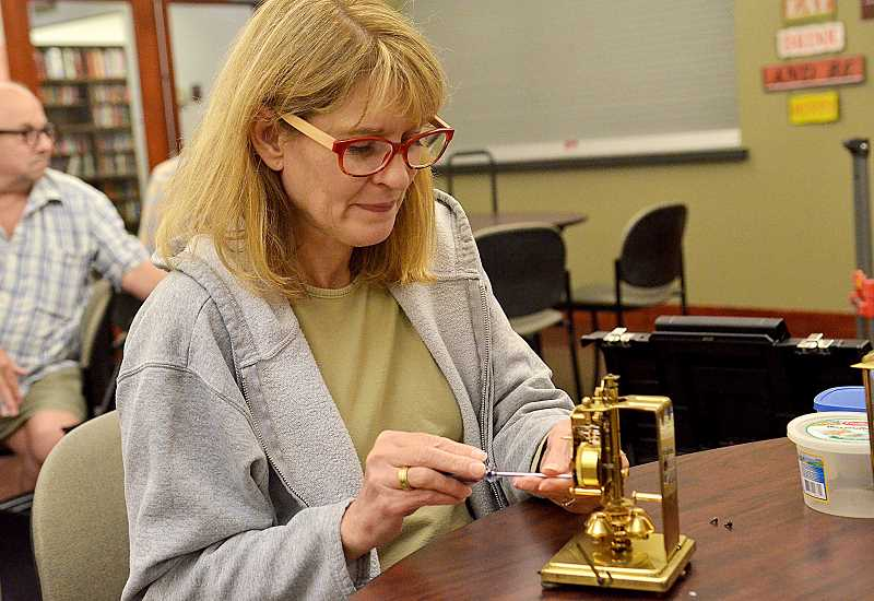 TIDINGS PHOTO: VERN UYETAKE - Marilyn Lindner works on her anniversary clock.