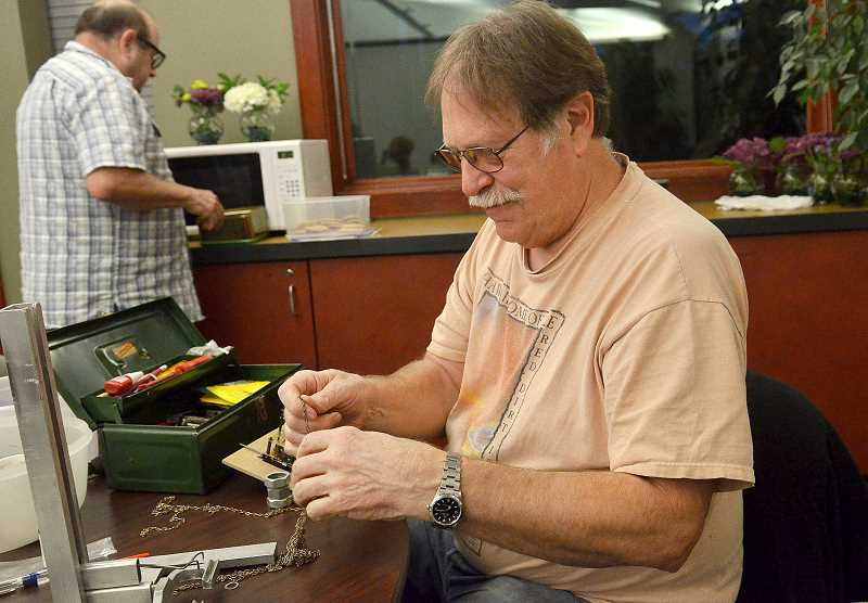 TIDINGS PHOTO: VERN UYETAKE - Mitch Wiegand of West Linn works on an old cuckoo clock.