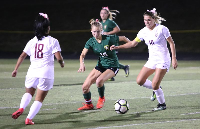 PAMPLIN MEDIA: JIM BESEDA - Putnam's Sasha Stumpf (16) tries to split Milwaukie's Suleika Mora (18) and MaKenna Presley during the second half of Tuesday's Northwest Oregon Conference girls' soccer game at Putnam.