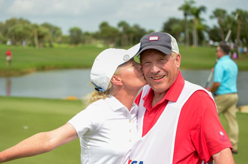 COURTESY: UNITED STATES GOLF ASSOCIATION - Champion Lara Tennant plants a kiss on the cheek of her father and caddy, George Mack Sr., after winning the U.S. Senior Women's Amateur championship.