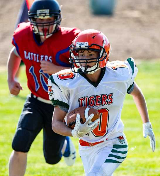 LON AUSTIN/CENTRAL OREGONIAN - Gabriel Walker-Hopkins carries the ball for a big gain in the Dayville/Monument game against Mitchell/Spray/Wheeler. Both teams are taking advantage of the opportunity to play six-man football this year.