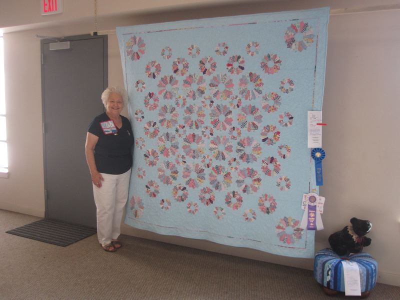COURTESY PHOTO - Doris Hale, a Rainier quilter, stands with a finished project made from pieces of her mothers dresses, which she completed after her mother died. Hale, who is this years featured artist, will have 40 quilts on display this weekend during the annual quilt show hosted by the Columbia River PIecemakers Quilt Guild.