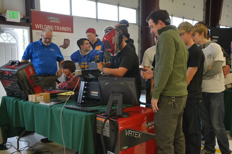 SPOTLIGHT PHOTO: COURTNEY VAUGHN - Cameron Sisco, a St. Helens High School student, tries his hand at simulated welding during a Makers Gone Pro event hosted at OMIC in Scappoose for Manufacturing Day. Pictured to the right: David Ciolek of Lincoln Electric Company guides students through demonstrations.