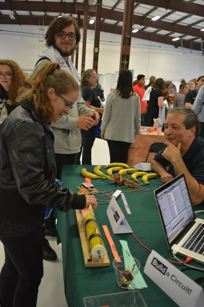 SPOTLIGHT PHOTO: COURTNEY VAUGHN - Cheyenne Packard, a Rainier High School student, tests out a lazer harp at a PDX Makers booth. Sitting opposite Packard, Mitch Bayersdorfer watches students experiment. s booth.