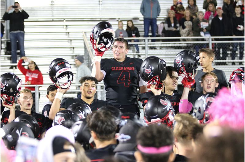 PAMPLIN MEDIA: JIM BESEDA - Clackamas players (left to right) Noah Hobbs, Justice Pagan, Jake Bushman, Brian Espinoza, and Richard Kennewell lead the team and students in the signing of the school fight song after Thursday's 38-12 'Senior Night' home win over Reynolds.