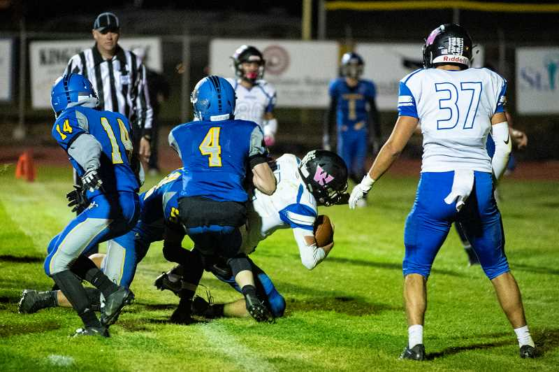 LON AUSTIN/CENTRAL OREGONIAN - R.J. Veliz dives across the goal line for the go-ahead touchdown midway through the third quarter of the woodburn Bulldogs 14-12 victory over the Crook County Cowboys Thursday night in Prineville.