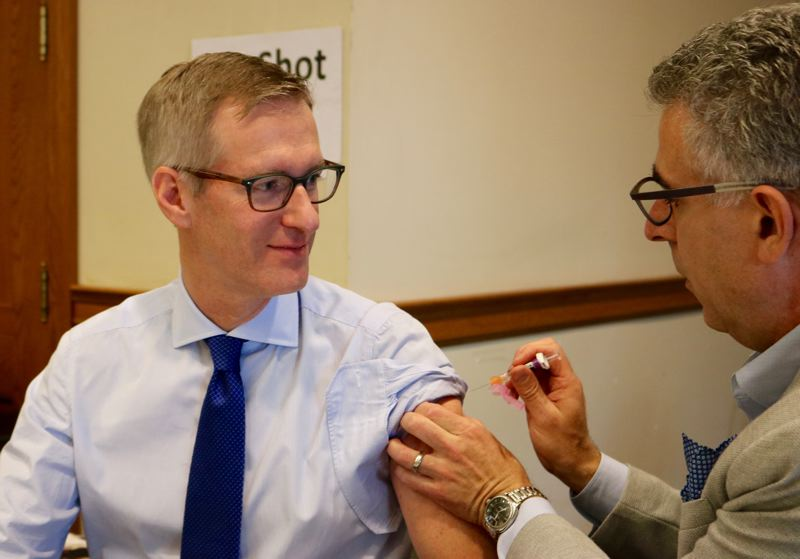 TRIBUNE PHOTO: ZANE SPARLING - Mayor Ted Wheeler receives his annual flu shot from nurse practioner Joel Michels on Friday, Oct. 12 at Portland City Hall.