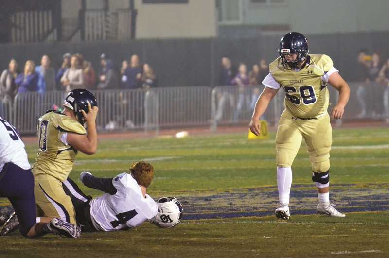 HERALD PHOTO: TANNER RUSS - Canby's Kyler Boyd stands over Lake Oswego quarterback Quinn Gunter after sacking him in the back field.