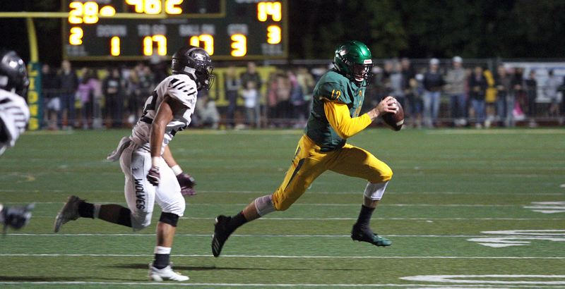 TIDINGS PHOTO: MILES VANCE - West Linn senior quarterback Ethan Long runs to daylight during his team's 45-20 win over Tualatin at West Linn High School on Friday night.