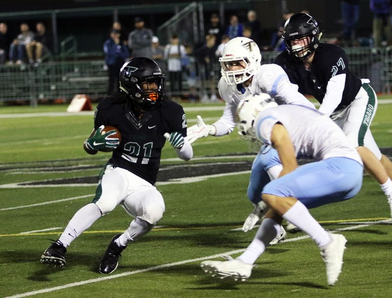 TIMES PHOTO: DAN BROOD - Tigard senior Malcolm Stockdale looks to get past a pair of Lakeridge defenders during Friday's game.