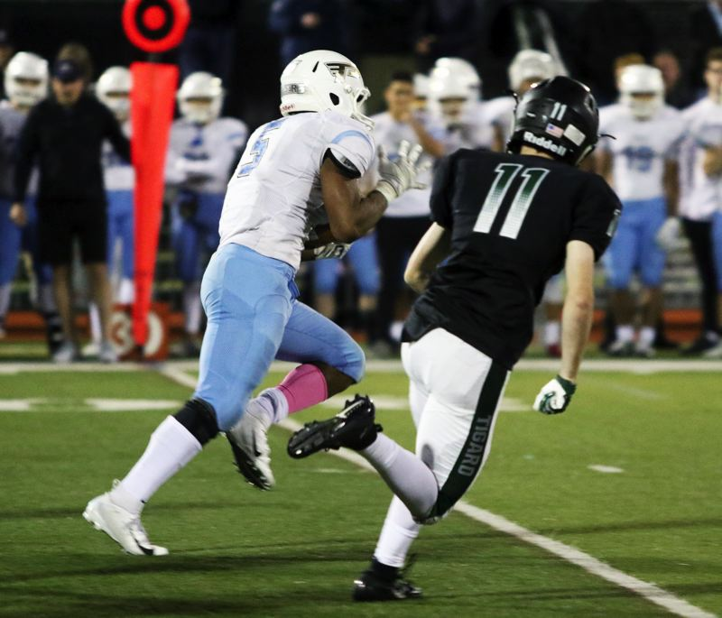 TIMES PHOTO: DAN BROOD - Lakeridge junior Jalen John (left) breaks into the clear on his way to scoring on an 80-yard run during the Pacers' win at Tigard on Friday.
