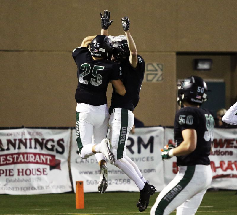 TIMES PHOTO: DAN BROOD - Tigard sophomore Spencer Kuffel (left) and senior Luke Ness celebrate following Ness' touchdown catch during Friday's game with Lakeridge.