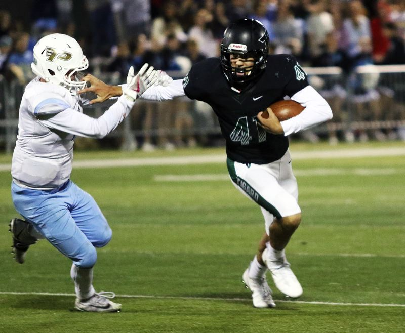 TIMES PHOTO: DAN BROOD - Tigard sophomore quarterback Drew Carter (right) tries to get away from a Lakeridge defender during Friday's game.