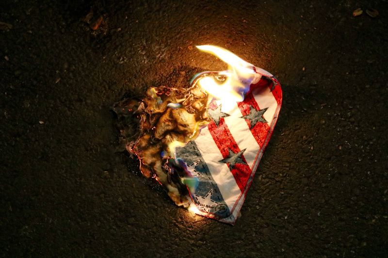 TRIBUNE PHOTO: ZANE SPARLING - Members of Antifa burned an American flag at one point during a protest on Saturday, Oct. 13 in downtown Portland.