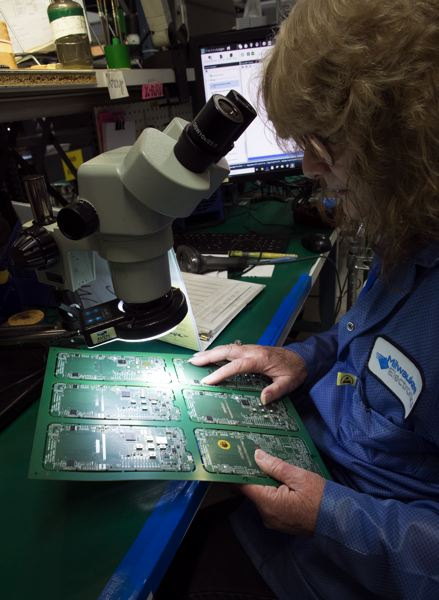 JAIME VALDEZ - Barbara Nichols, a quality control worker for Screaming Circuits, looks over a circuit board at the Canby facility.