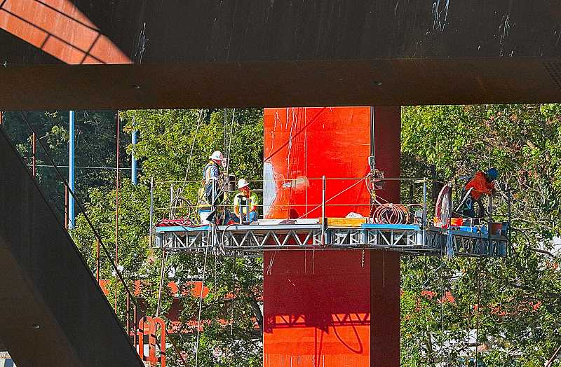 DAVID F. ASHTON - Perched overhead on scaffolding, workers finish patching irregularities on the face of a Sellwood Bridge pier.