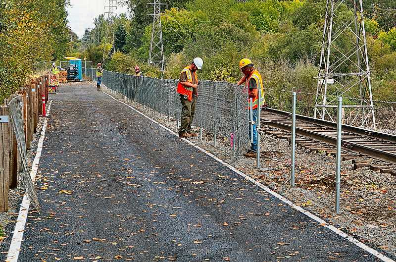 DAVID F. ASHTON - Workers replace the fence between the Springwater Corridor Trail path and the Oregon Pacific Railroad tracks, one of the project's final touches.